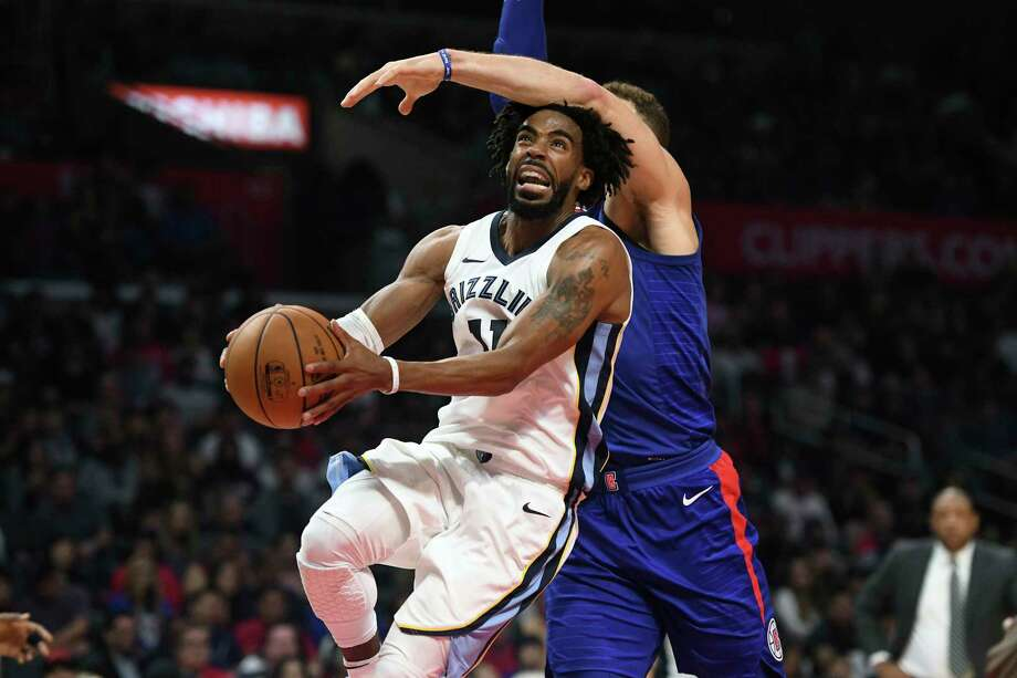 Grizzlies guard Mike Conley, left, draws a foul from behind by Clippers forward Blake Griffin while driving to the basket during the second half Saturday. Photo: Michael Owen Baker, FRE / FR171390 AP