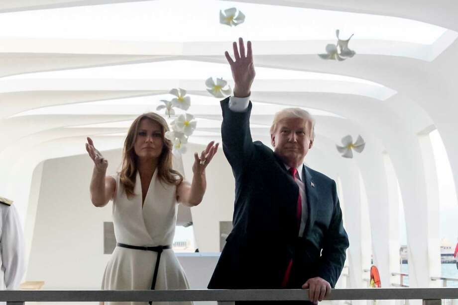 U.S. President Donald Trump and first lady Melania Trump throw flower pedals while visiting the Pearl Harbor Memorial in Honolulu, Hawaii Friday, Nov. 3, 2017. Trump paid a solemn visit Friday to Pearl Harbor and its memorial to the USS Arizona, a hallowed place he said he had read about, discussed and studied but had never visited until just before opening his first official visit to Asia. (AP Photo/Andrew Harnik) Photo: Andrew Harnik, STF / Copyright 2017 The Associated Press. All rights reserved.