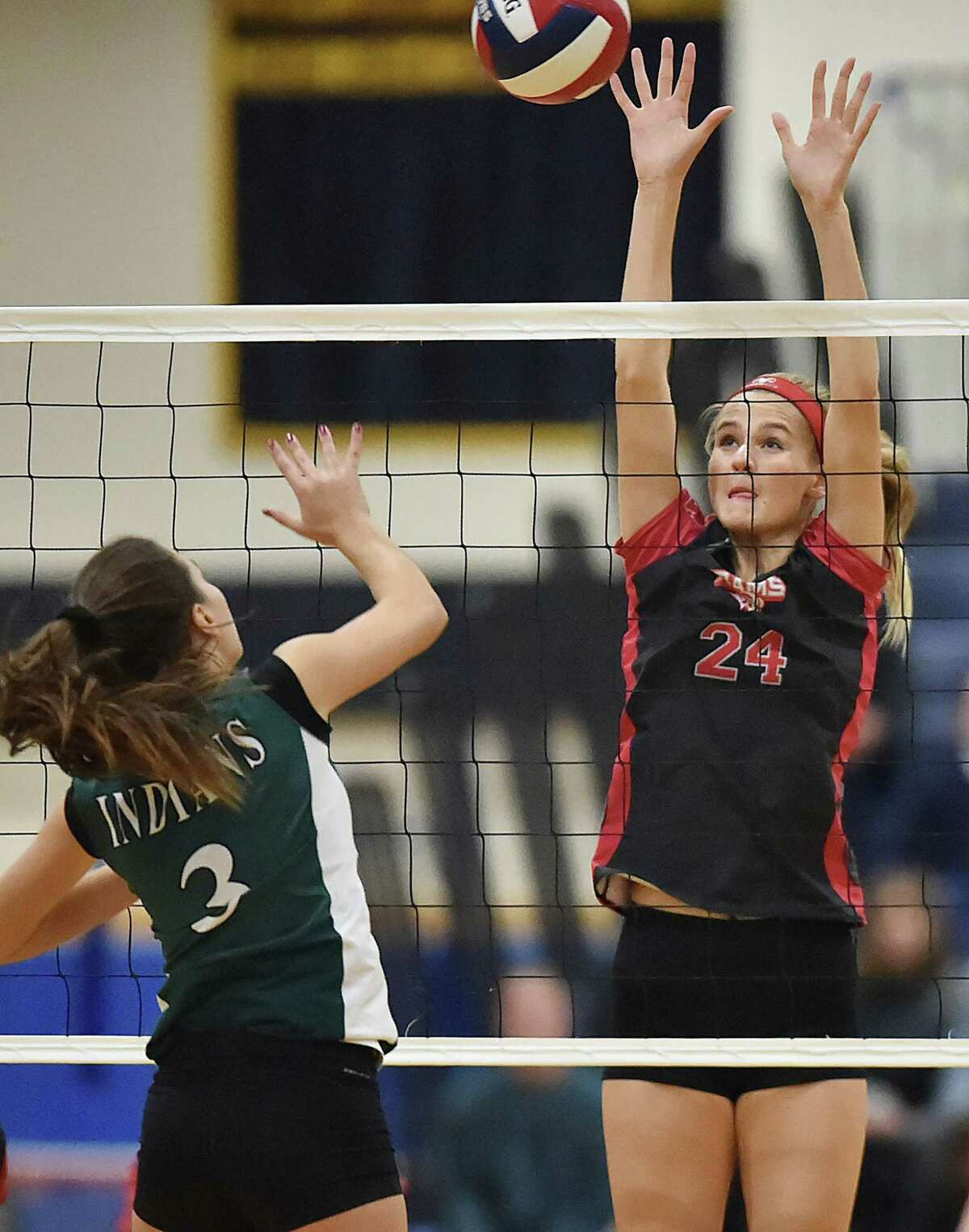 Cheshire's Brady McQuade, right, blocks a shot by Guilford's Jessica Decensi during Saturday's SCC championship game at East Haven High School.
