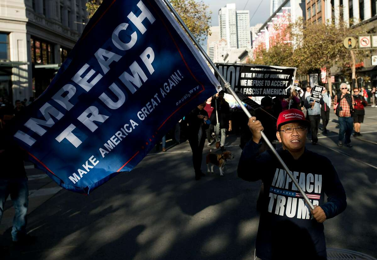 John from Mountain View, who declined to give a last name, joins more than a hundred protesters against President Donald Trump marching down Market St. in San Francisco on Saturday, Nov. 4, 2017.