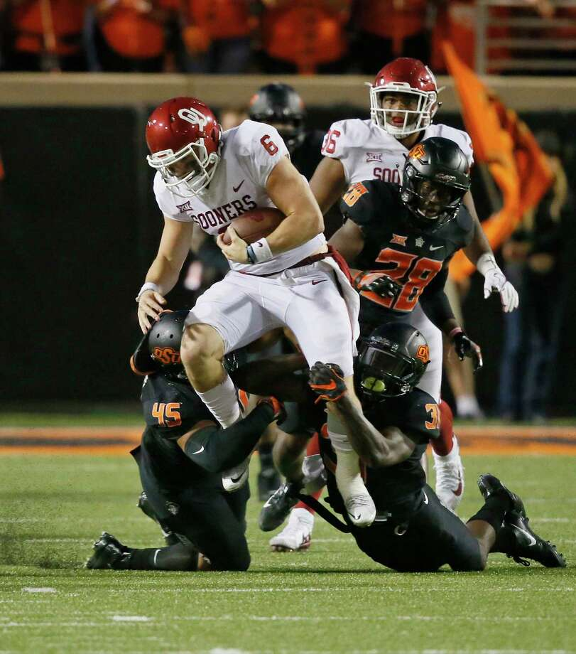 Oklahoma quarterback Baker Mayfield, at left, enjoys a productive Saturday in leading the Sooners past Oklahoma State, passing for 598 yards and five touchdowns, as well as rushing for a score. But quarterback Mason Rudolph, at right, did his best to help the Cowboys keep pace, passing for 448 yards and five touchdowns. Photo: Sue Ogrocki, STF / AP2017