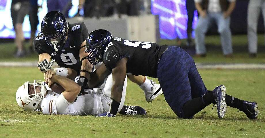 defensive tackle Chris Bradley (56) and defensive end Mat Boesen (9) sack Texas quarterback Shane Buechele (7) during the second quarter at Amon G. Carter Stadium in Fort Worth, Texas, on Saturday, Nov. 4, 2017. (Max Faulkner/Fort Worth Star-Telegram/TNS) Photo: Max Faulkner/TNS