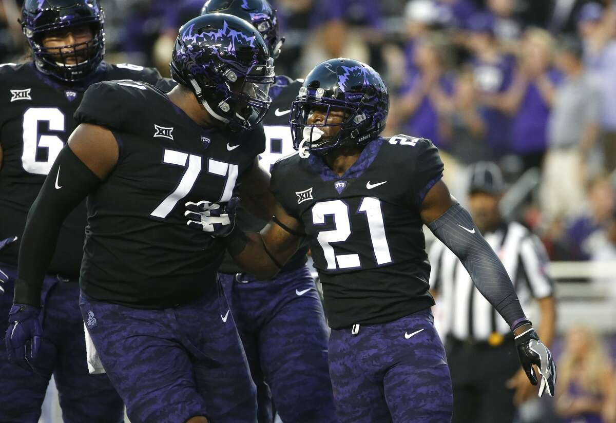 TCU's Lucas Niang (77) and running back Kyle Hicks (21) celebrate Hicks' touchdown during the first half of an NCAA college football game against Texas on Saturday, Nov. 4, 2017, in Fort Worth, Texas. (AP Photo/Ron Jenkins)