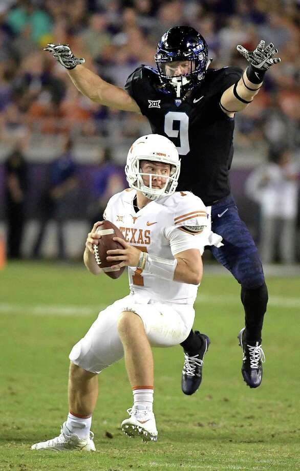 TCU defensive end Mat Boesen, right, is about to spring a big surprise on Texas quarterback Shane Buechele in the first half of Saturday night's game at Amon G. Carter Stadium in Fort Worth. Photo: Max Faulkner, MBR / Fort Worth Star-Telegram