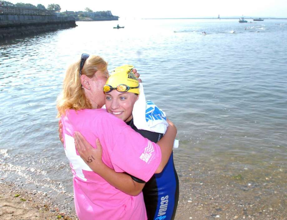 Breast cancer survivor Tori Kroll of New Canaan, left, hugs and kisses her daughter, Livi Kroll, 17, after Livi finshed her swim during the Greenwich-Stamford Swim Across America event, dedicated to raising money and awareness for cancer research through swimming, at Cummings Point, Stamford, Saturday morning, June 26, 2010. Photo: Bob Luckey / Greenwich Time