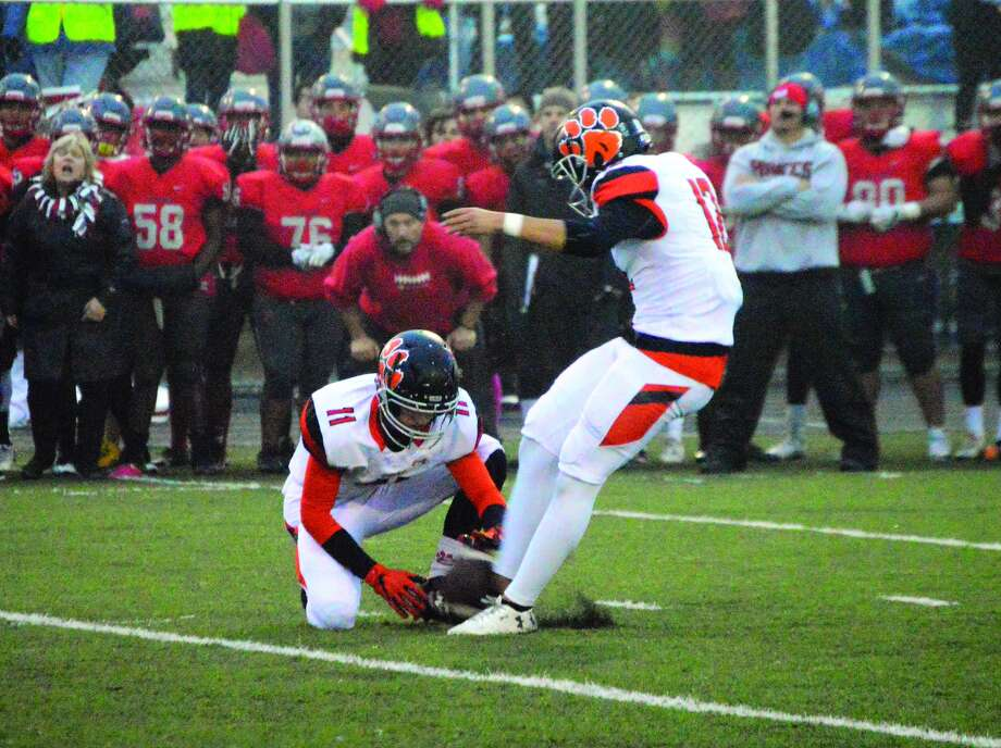 Edwardsville's Devin Parker, right, hits the go-ahead field goal late in the fourth quarter of Saturday's IHSA Class 8A postseason game at Palatine. Blake Neville has the hold for EHS.