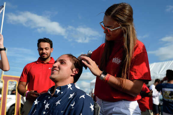 Macy Edgerly, of the Zeta Tau Alpha sorority, shaves Jordan Curl's head during Lamar's homecoming celebrations on Saturday. Curl agreed to have his head shaved after ZTA reached their fundraising goal for breast cancer.  Photo taken Saturday 11/4/17 Ryan Pelham/The Enterprise