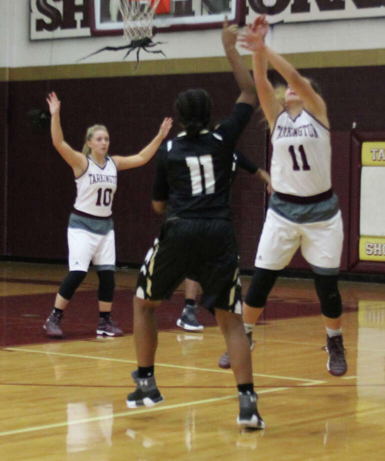 Maddie Vandver (10) and Ajia Whitmore (11) of the Tarkington LadyHorns jump to block a shot from one of the Woodville Lady Eagles. Photo: Jacob McAdams