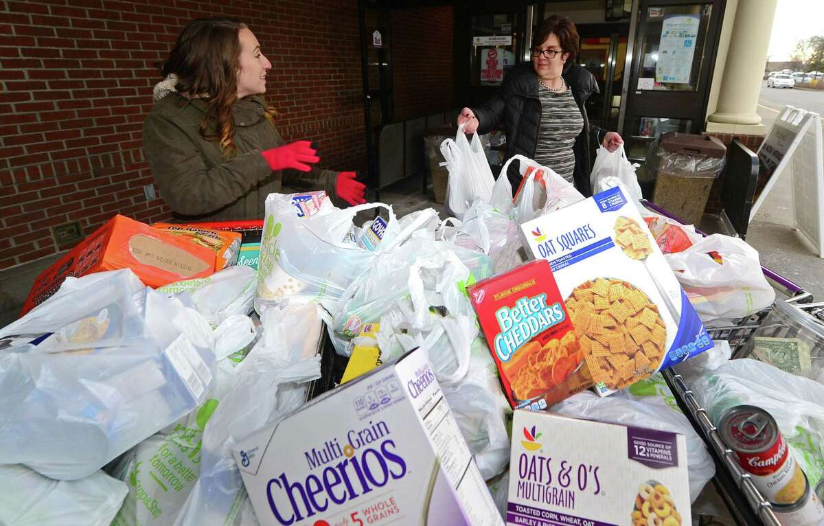 """Bridgeport Rescue Missions volunteer coordinator, Courtney Pandolfi accepts donations from Dianne Migliorelli during the Mission's Stuff a Truck food drive Thursday, February 2, 2017, at the Stop & Shop on Main Avenue in Norwalk, Conn. The mission's """"ThanksGiving"""" food and coat-collection drive will take place November 15-18 and November 20-21 at the Webster Bank Arena from 12:30 to 2 p.m. daily."""