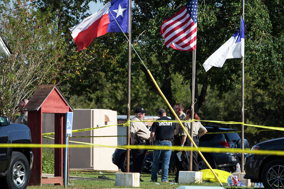 Law enforcement officials stand next to a covered body at the scene of a fatal shooting at the First Baptist Church in Sutherland Springs, Texas, on Sunday, Nov. 5, 2017. (Nick Wagner/Austin American-Statesman via AP) Photo: Nick Wagner, MBO / Austin American-Statesman
