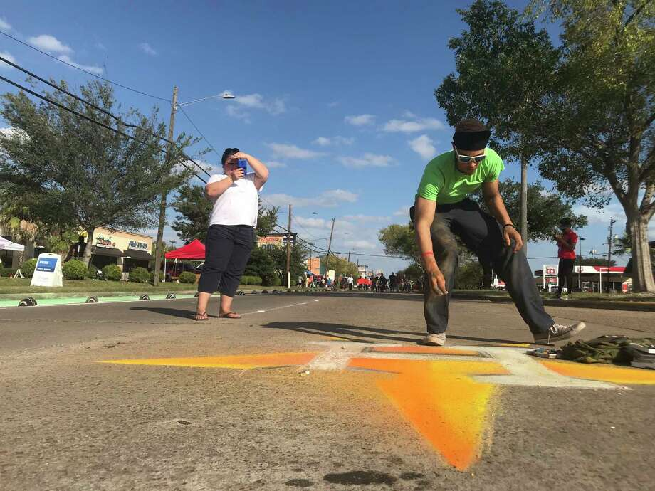 Tim Walker, 27, sketches a Houston Astros emblem in the westbound fast lane of Bellaire near Renwick during Houston Sunday Streets on Sunday. The event, which closed about a mile of Bellaire in the Gulfton area, was the first time the wellness initiative came to Houston's most diverse neighborhood. Photo: Dug Begley / Houston Chronicle