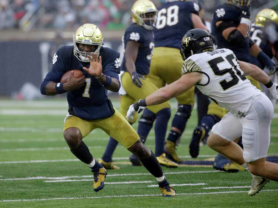 Notre Dame quarterback Brandon Wimbush , left, carries a ball against Wake Forest linebacker Grant Dawson during the first half of an NCAA college football game Saturday, Nov. 4, 2017, in South Bend, Ind. (AP Photo/Nam Y. Huh) Photo: Nam Y. Huh, STF / Copyright 2017 The Associated Press. All rights reserved.