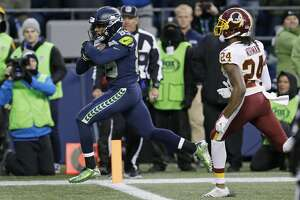 Seattle Seahawks wide receiver Doug Baldwin, left, runs in for a touchdown ahead of Washington Redskins cornerback Josh Norman, right, in the second half of an NFL football game, Sunday, Nov. 5, 2017, in Seattle. (AP Photo/Stephen Brashear)