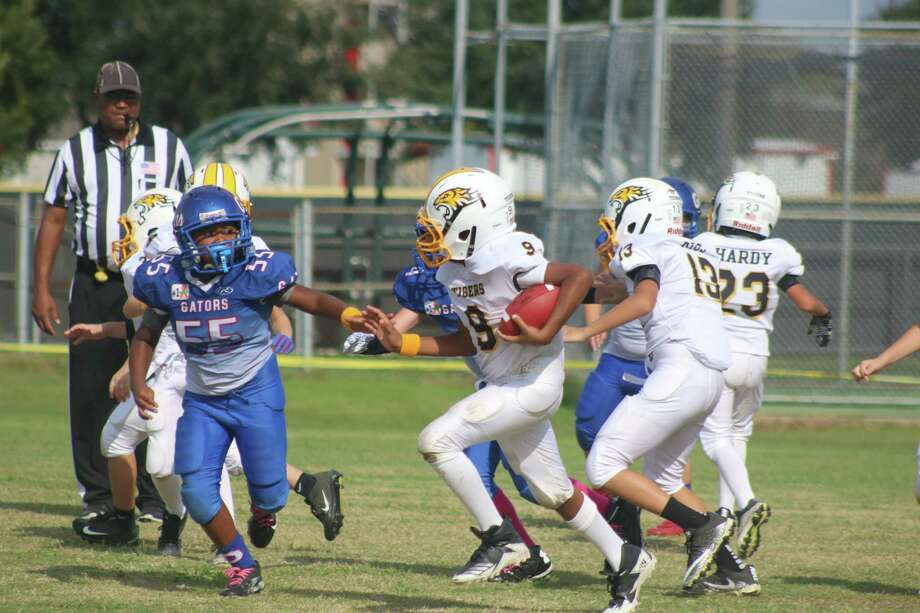 Lashaun Panuco hegins the journey on his 45-yard touchdown scamper in the third quarter Saturday afternoon. The Deer Park Elementary School student scored three times to send his teammates to the Final Four. Photo: Robert Avery