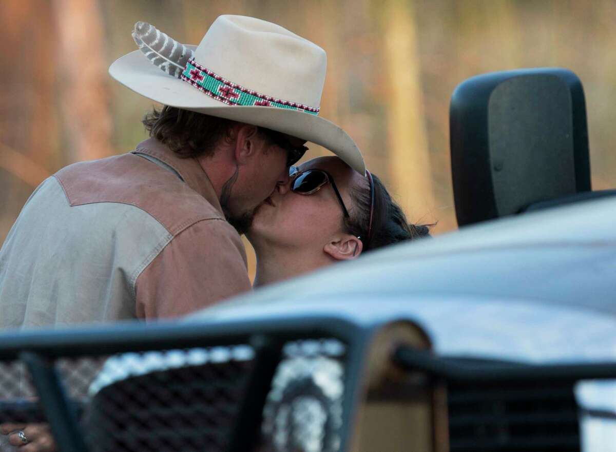 Johnnie Langendorff, who pursued the suspect of the Sutherland Springs First Baptist Church church shooting that killed at least 25 people, gets a kiss Sunday, Nov. 5, 2017 as he is picked up from the scene where the suspect died near the intersection of FM 539 and Sandy Elm Road in Guadalupe County. Officials have not said how the suspect died.