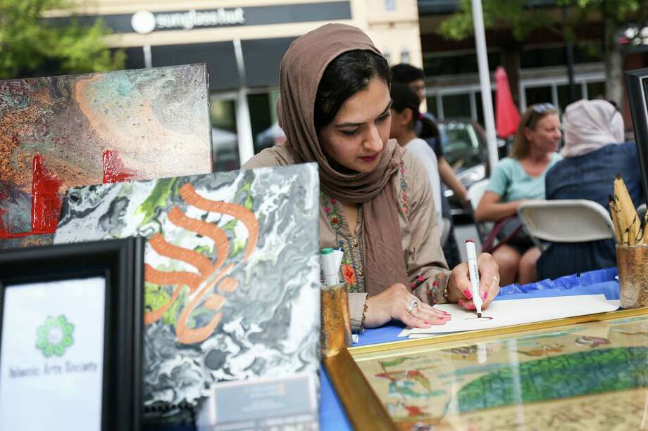 Sana Mirza, of the Islamic Arts Society of Houston, writes people's names in Thuluth, a style of Islamic calligraphy, during the Cultural and Heritage Festival on Sunday, Nov. 5, 2017, at Market Street in The Woodlands. Photo: Michael Minasi, Staff Photographer / © 2017 Houston Chronicle