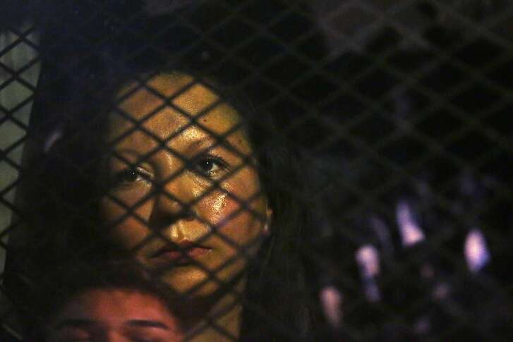 FILE - In this Feb. 8, 2017 file photo, Guadalupe Garcia de Rayos is locked in a van that is stopped in the street by protesters outside the Immigration and Customs Enforcement facility in Phoenix. Advocacy groups said that Immigration and Customs Enforcement officers are rounding up people in large numbers around the country as part of stepped-up enforcement under President Donald Trump, a decade-old deterrence program for prosecuting immigrants in its get-tough approach to immigration. But it's unclear just how effective that program is. (Rob Schumacher/The Arizona Republic via AP, File)