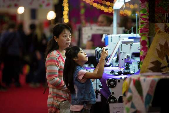 Emily Deng, 8, experiments with a swing machine at the International Quilt Festival Houston on Sunday in Houston.