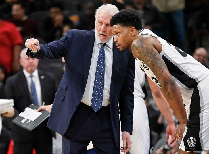 San Antonio Spurs forward Kawhi Leonard (2) scores as Phoenix Suns center Alex Len (21) and guard Devin Booker (1) defend during the first half of an NBA basketball game Friday, Jan. 5, 2018, in San Antonio. San Antonio won 103-89. (AP Photo/Eric Gay)