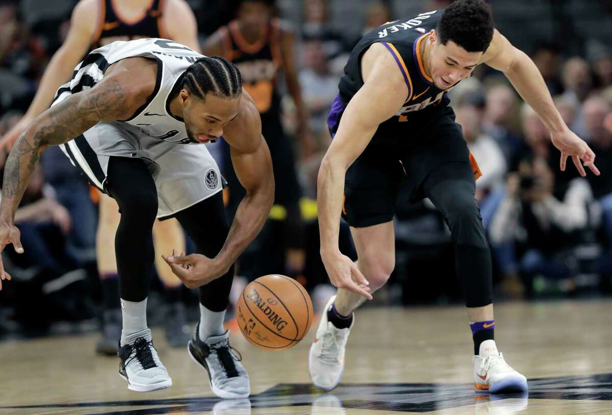 San Antonio Spurs forward Kawhi Leonard, left, and Phoenix Suns guard Devin Booker, right, chase the ball during the first half of an NBA basketball game Friday, Jan. 5, 2018, in San Antonio. (AP Photo/Eric Gay)
