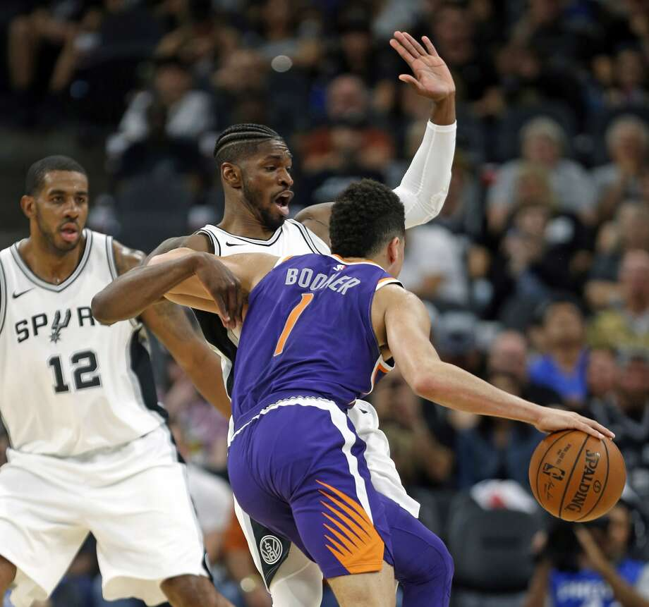 San Antonio Spurs Brandon Paul draws a charge from Phoenix Suns' Devin Booker during the first half of an NBA game on Sunday, Nov. 5, 2017 in San Antonio. (AP Photo/Ronald Cortes)