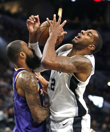 San Antonio Spurs' LaMarcus Aldridge(12) of the San Antonio Spurs is fouled by Phoenix Suns' Tyson Chandlerin a NBA game on Sunday, Nov. 5, 2017 in San Antonio. (AP Photo/Ronald Cortes)