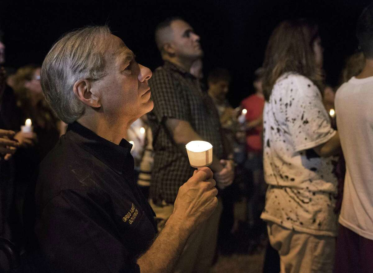 Texas Gov. Greg Abbott participates in a candlelight vigil for the victims of a fatal shooting at the First Baptist Church in Sutherland Springs, Sunday.