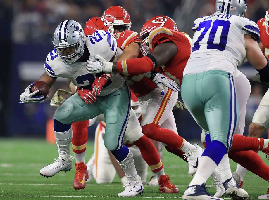 Ezekiel Elliott of the Dallas Cowboys fights to stay on his feet against Kansas City Chiefs defenders in the fourth quarter at AT&T Stadium on November 5, 2017 in Arlington, Texas. (Photo by Ronald Martinez/Getty Images) Photo: Ronald Martinez, Staff / 2017 Getty Images