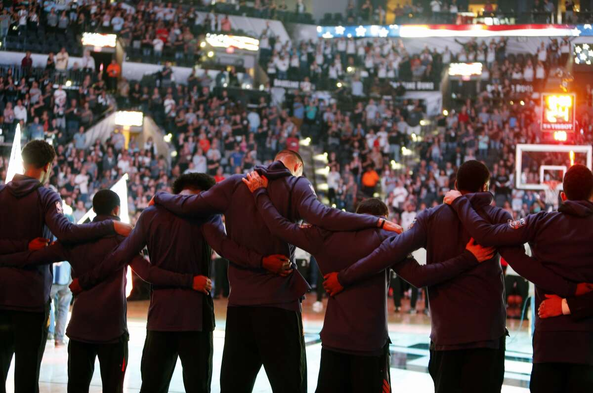 Members of the Phoenix Suns stand arm-in-arm during a moment of silence for the victims of a deadly church shooting in Texas before an NBA basketball team against the San AntonioSpurs, Sunday, Nov. 5, 2017 in San Antonio. (AP Photo/Ronald Cortes)