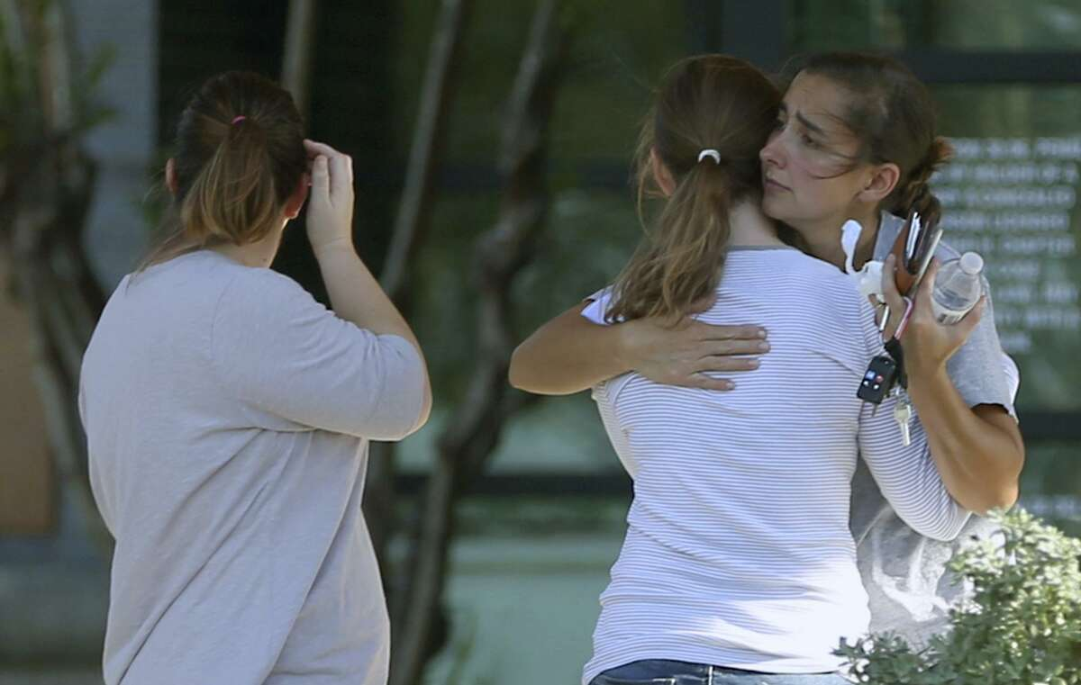 People hug Sunday, Nov. 5, 2017 outside Connally Memorial Medical Center in Floresville Texas. Several of the people injured in the First Baptist Church of Sutherland Springs mass shooting which killed at least 28 were taken the the facility.