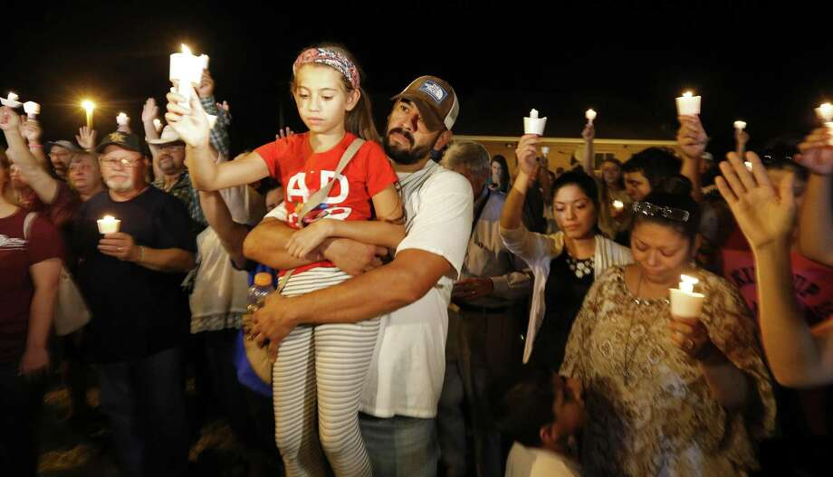 Ramiro Martinez hold his daughter Sophia, 9, during a candle light vigil for the shooting at the First Baptist Church of Sutherland Springs Sunday Nov 5, 2017. Photo: Edward A. Ornelas, Staff / San Antonio Express-News / © 2017 San Antonio Express-News
