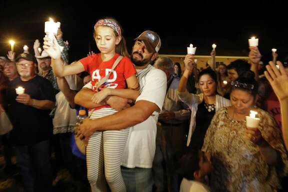 Ramiro Martinez hold his daughter Sophia, 9, during a candle light vigil for the shooting at the First Baptist Church of Sutherland Springs Sunday Nov 5, 2017.