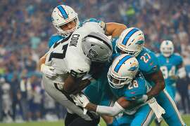 MIAMI GARDENS, FL - NOVEMBER 05: Tight end Jared Cook #87 of the Oakland Raiders is tackled by cornerback Bobby McCain #28 of the Miami Dolphins and Maurice Smith #27 of the Miami Dolphins at Hard Rock Stadium on November 5, 2017 in Miami Gardens, Florida.  (Photo by Chris Trotman/Getty Images)