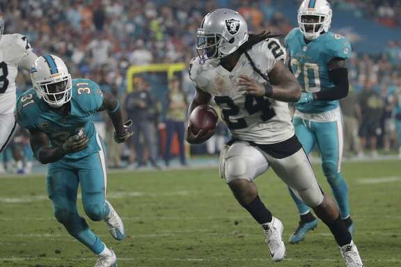Oakland Raiders running back Marshawn Lynch (24) runs for a touchdown ahead of Miami Dolphins free safety Reshad Jones (20) and free safety Michael Thomas (31), during the second half of an NFL football game, Sunday, Nov. 5, 2017, in Miami Gardens, Fla. (AP Photo/Lynne Sladky)