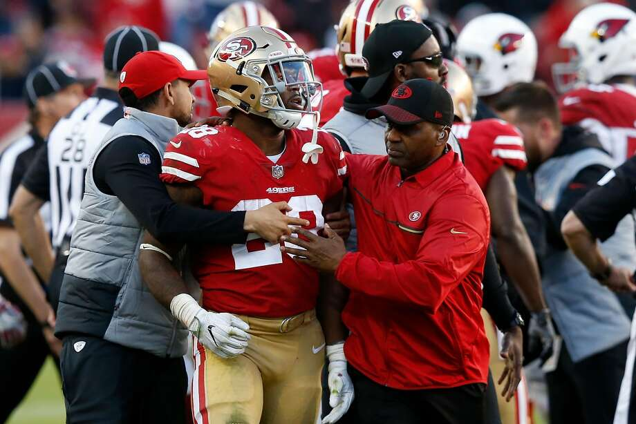 Carlos Hyde of the San Francisco 49ers is walked off the field by San Francisco 49ers staff after a scuffle due to a late hit on C.J. Beathard #3 of the San Francisco 49ers by Antoine Bethea #41 of the Arizona Cardinals during their NFL game at Levi's Stadium on November 5, 2017 in Santa Clara, California. Hyde was ejected from the game for his role. Photo: Lachlan Cunningham, Getty Images