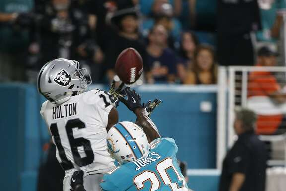 Oakland Raiders wide receiver Johnny Holton (16) grabs a touchdown pass as Miami Dolphins free safety Reshad Jones (20) attempts to defend, during the first half of an NFL football game, Sunday, Nov. 5, 2017, in Miami Gardens, Fla. (AP Photo/Wilfredo Lee)
