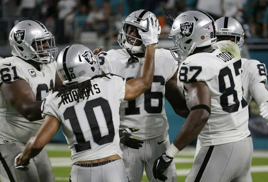 Oakland Raiders center Rodney Hudson (61), wide receiver Seth Roberts (10), and tight end Jared Cook (87), congratulate wide receiver Johnny Holton (16), after Holton scored a touchdown, during the first half of an NFL football game against the Miami Dolphins, Sunday, Nov. 5, 2017, in Miami Gardens, Fla. (AP Photo/Lynne Sladky) Photo: Lynne Sladky, Associated Press