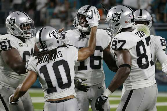 Oakland Raiders center Rodney Hudson (61), wide receiver Seth Roberts (10), and tight end Jared Cook (87), congratulate wide receiver Johnny Holton (16), after Holton scored a touchdown, during the first half of an NFL football game against the Miami Dolphins, Sunday, Nov. 5, 2017, in Miami Gardens, Fla. (AP Photo/Lynne Sladky)