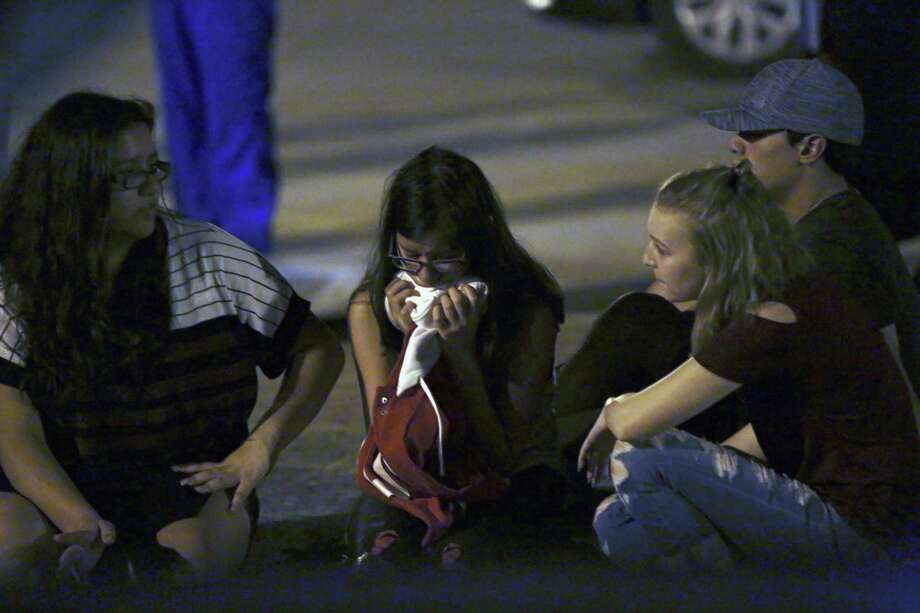 Deanna (left) and Hannah (right) sit with an unidentified friend at the post office following a vigil for those affected by the mass shooting Sunday in Sutherland Springs. Photo: Bob Owen /San Antonio Express-News / San Antonio Express-News