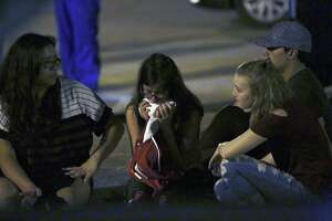 Deanna (left) and Hannah (right) sit with an unidentified friend at the post office following a vigil for those affected by the mass shooting Sunday in Sutherland Springs.