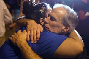"""Texas Governor Greg Abbott comforts a local resident during a candlelight vigil held on November 5, 2017, following the mass shooting inside the First Baptist Church in Sutherland Springs, Texas. """"There are 26 lives that have been lost. We don't know if that number will rise or not, all we know is that's too many, and this will be a long, suffering mourning for those in pain,"""" Abbott said during a press conference.  / AFP PHOTO / SUZANNE CORDEIRO        (Photo credit should read SUZANNE CORDEIRO/AFP/Getty Images)"""