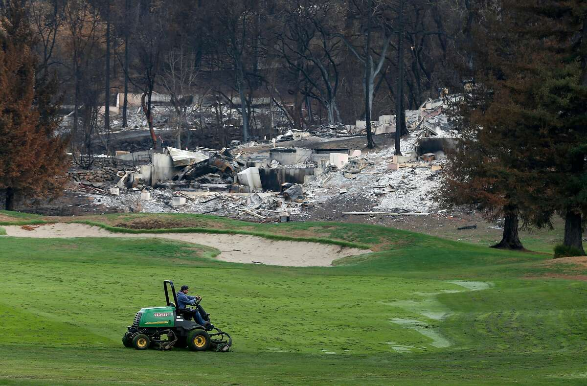 A groundskeeper mows grass on the fairway of the 1st hole at the Fountaingrove Golf Club in Santa Rosa, Calif. on Thursday, Nov. 2, 2017. Fountaingrove hopes to reopen the course in mid-November despite its clubhouse and other buildings getting burned to the ground in last month's Tubbs Fire.