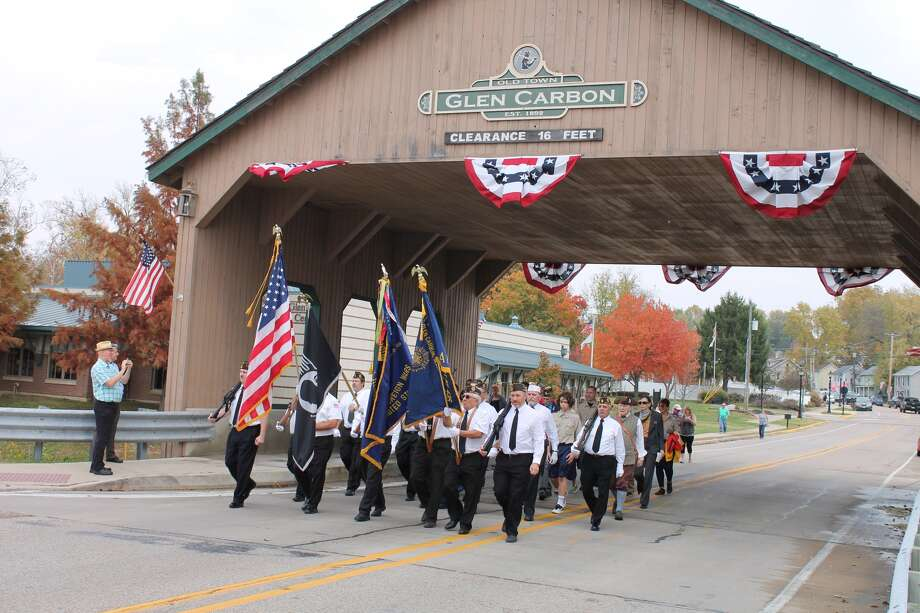 Sunday's showers held off long enough for the Glen Carbon pre-Veterans Day ceremony to be completed. Every year, Members of VFW Post 2222 and American Legion Post 435 march from the Legion Hall to the Glen Carbon Veterans Monument on the Sunday before the holiday. Pictured are an overall view of the ceremony and VFW and American Legion members marching through the Glen Carbon Covered Bridge. Boy Scouts from Troop 1034 watch from the proceedings. Photo: Bill Tucker • Btucker@edwpub.net