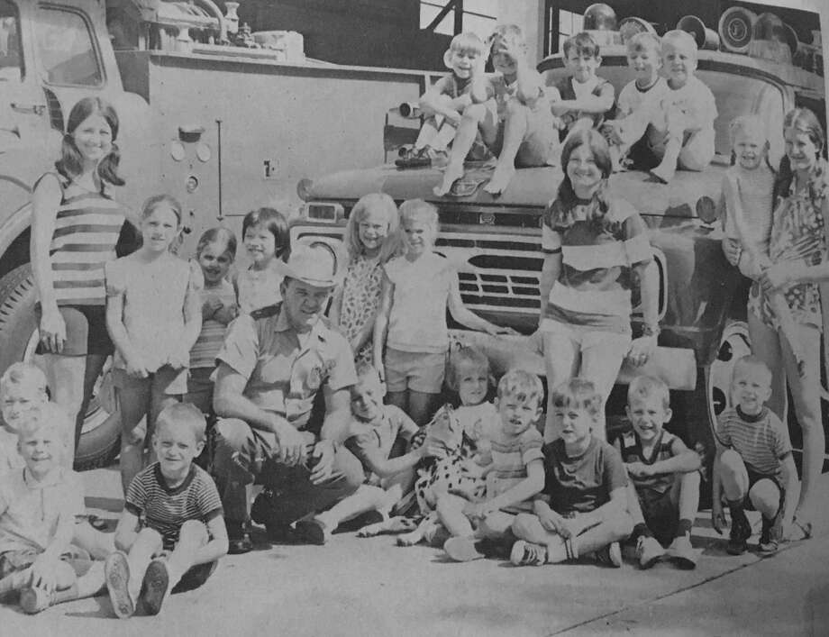 Five and six year olds from the YMCA visit the Conroe Fire Department with the Conroe Chief of Police Larry Evans Sr., center.
