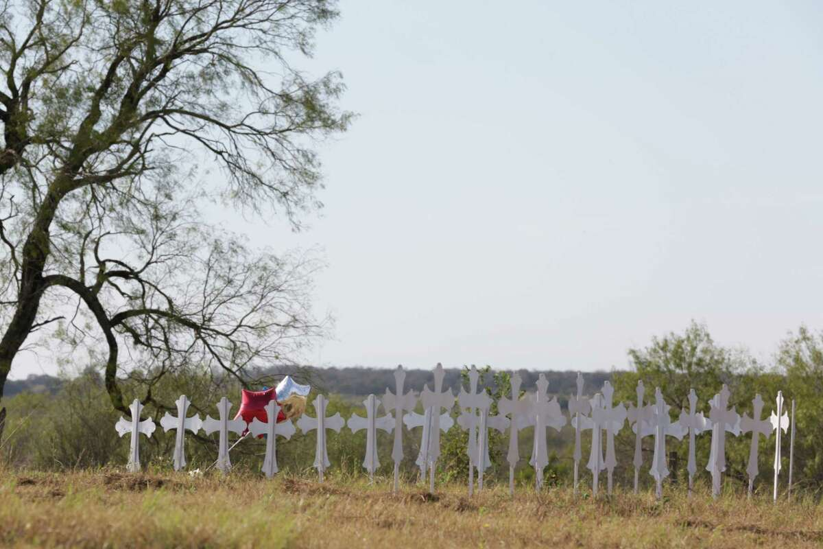 A resident of Sutherland Springs places balloons and a teddy bear next to 26 crosses that have been set up near the Ball Park for those killed in the mass shooting at the First Baptist Church in Sutherland Springs, Texas, on Monday, Nov. 6, 2017.
