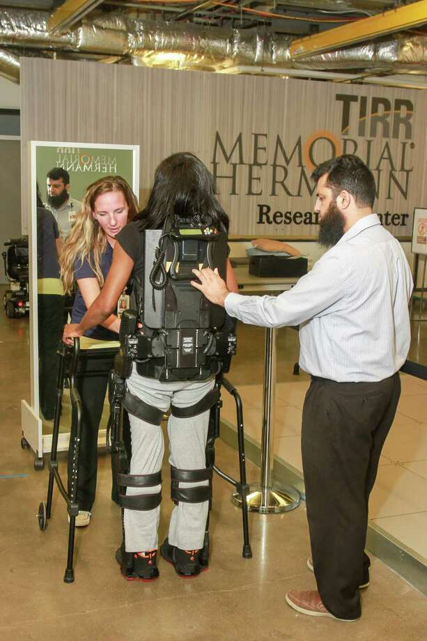 Physical therapist Erin Edenfield, left, uses a mirror to aid Vikki McFarland, a study participant, in walking, wearing a Ekso wearable robotic device at TIRR Memorial Hermann. Taimoor Afzal, right, is assisting. Photo: Gary Fountain, For The Chronicle/Gary Fountain / Copyright 2017 Gary Fountain