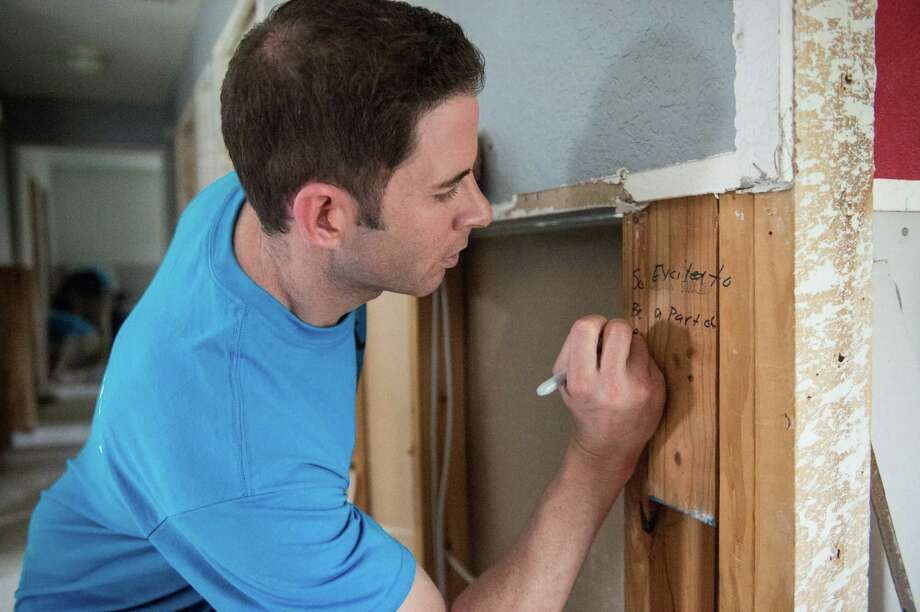 """Tarek El Moussa writes a message on the frame of Zipporah Smith's home in northeast Houston. El Moussa, co-star of HGTV's """"Flip or Flop,"""" came to Houston with a crew of 10 to spend a weekend helping repair the hurricane-flooded home. Photo: Michael Starghill Jr., Michael Starghill, Jr. / © Michael Starghill, Jr."""