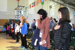 """Anna Wood of Fairfield, PTA president, flanked by her daughter Parker, 9, left, and Phoebe Fossi, 10, of Fairfield, gets emotional during the song """"America the Beautiful"""" at the McKinley School World's Fair, Saturday, Nov. 4, 2017, in Fairfield, Conn."""