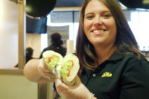New Which Wich franchise co-owner Shannon McCain shows off a sandwich she prepares to open her new shop on Fairmont.