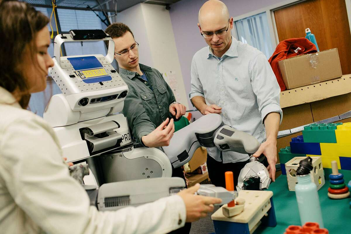 FILE -- From right, Pieter Abbeel, a professor at the University of California, Berkeley; Sergey Levin, post-doctoral researcher; and Ph.D. student Chelsea Finn work on a robot at a research lab on campus, May 20, 2015. Google and others, fighting for a small pool of researchers, are looking for automated ways to deal with a shortage of artificial intelligence experts. �Computers are going to invent the algorithms for us, essentially,� Abbeel said. (Peter Earl McCollough/The New York Times)